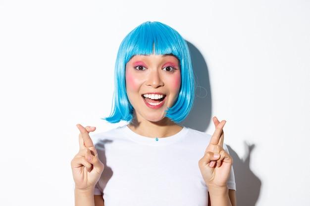 Zbliżenie: pełna nadziei śliczna azjatycka dziewczyna w niebieskiej peruce, czyniąc życzenie, kciuki powodzenia, stojąc.