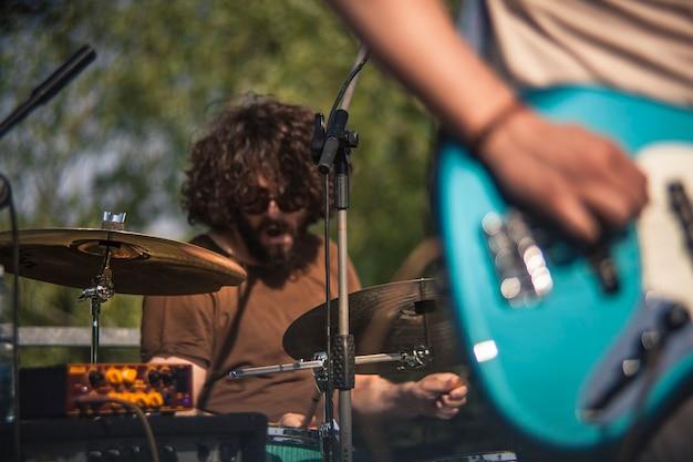 Zbliżenie perkusisty przefiltrowanego przez elementy jego zestawu perkusyjnego podczas koncertu