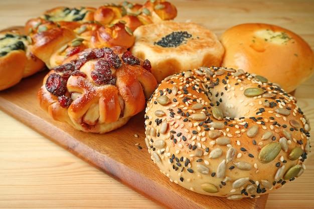 Zbliżenie pestki dyni i chleb sezamowy z bukietem słodkich i pikantnych pieczywa w tle