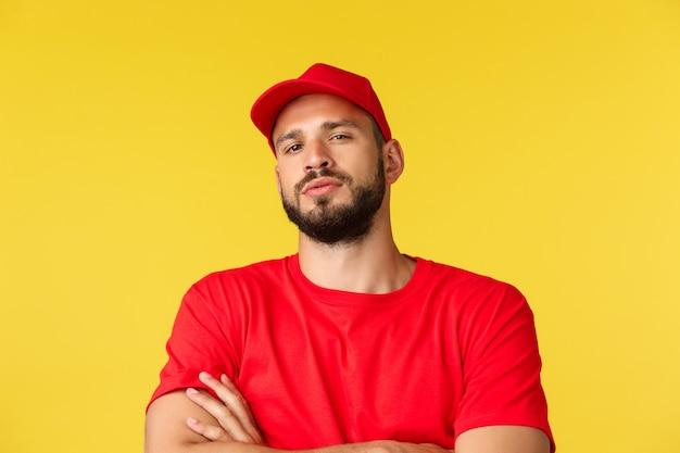Zbliżenie pewny siebie przystojny brodaty kurier mężczyzna kurier w czerwonej jednolitej czapce i koszulce wygl...