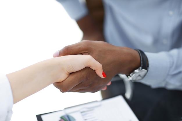 Zbliżenie.pewny uścisk dłoni między ludźmi biznesu w biurze