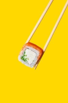Zbliżenie philadelphia roll z łososiem, serem i ogórkiem na pałeczkach na żółtym tle