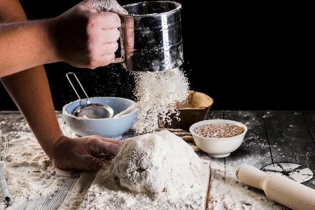 Zbliżenie piekarza przesiewa mąkę przez sito w celu przygotowania ciasta