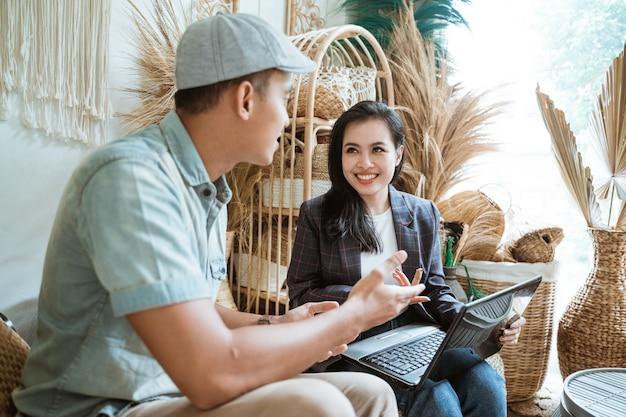 Zbliżenie piękna bizneswoman w marynarce na czacie ze swoim klientem podczas korzystania z laptopa w sklepie rzemieślniczym