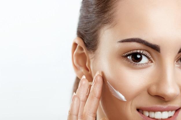 Zbliżenie piękna dziewczyna z kosmetykiem na miękkiej skóry naturalny makijaż dotykając twarzy