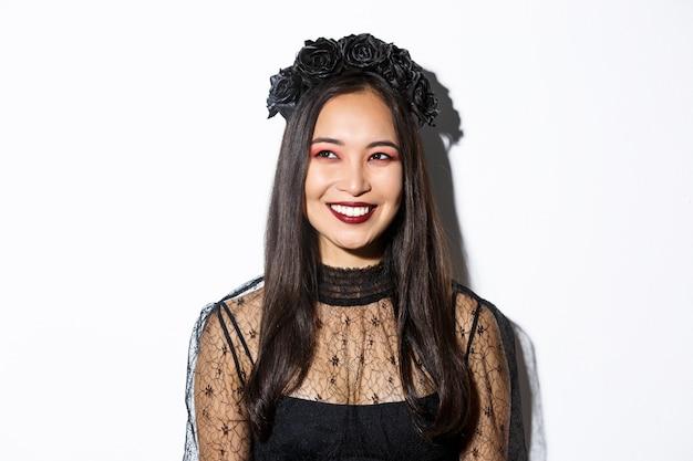Zbliżenie: piękna elegancka kobieta w stroju czarownicy i gotyckim makijażu, uśmiechnięta zadowolona, patrząc w lewy górny róg, świętująca halloween.