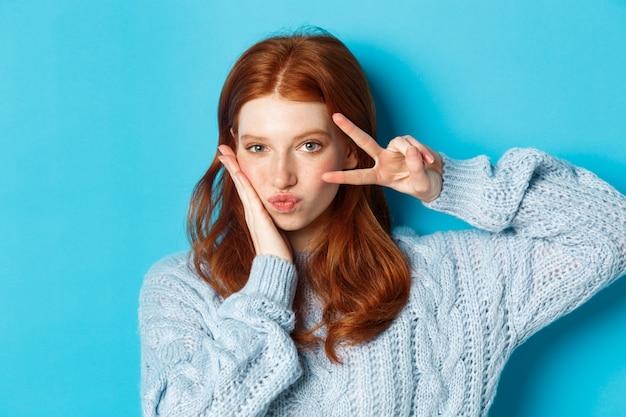 Zbliżenie: piękna i bezczelna dziewczyna z rudymi włosami, pokazująca znak pokoju kawaii i wpatrująca się w kamerę, stojąca na niebieskim tle.