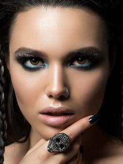 Zbliżenie piękna kobieta dotyka jej twarzy. idealny makijaż skóry i wieczorowy .. zmysłowość, pasja, modny makijaż młodzieżowy czy koncepcja kosmetologii.