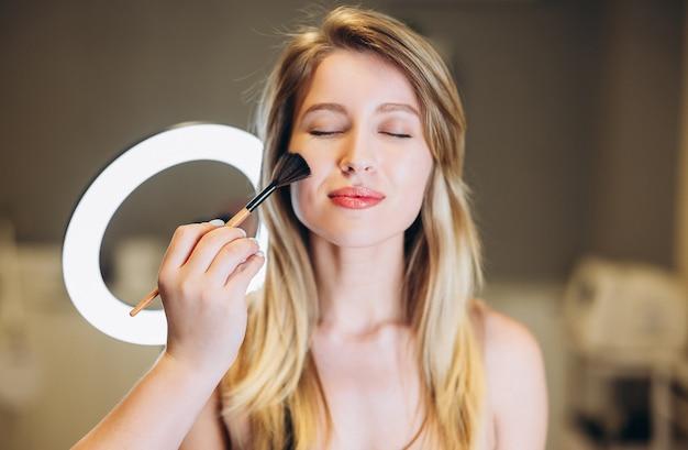 Zbliżenie: piękna kobieta o blond włosach i pędzlem do pudru w pobliżu twarzy. do nakładania pudru na piękną twarz za pomocą pędzla. blond z zamkniętymi oczami na makijaż.