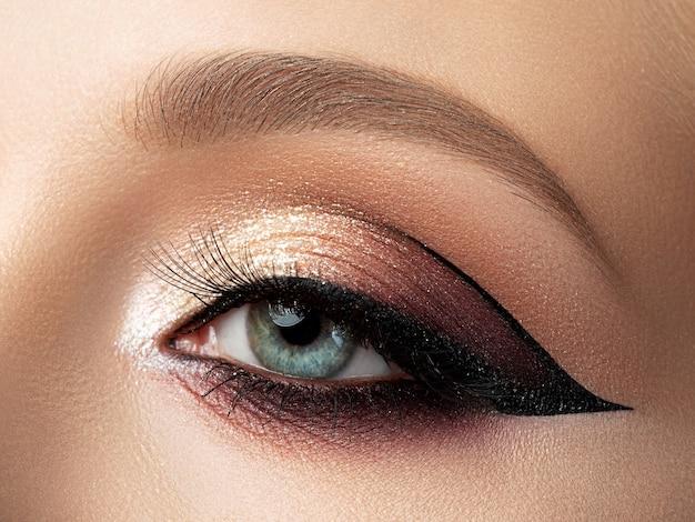 Zbliżenie piękna kobieta oko z wielobarwnym makijażem mody i nowoczesnym skrzydłem eyeliner.
