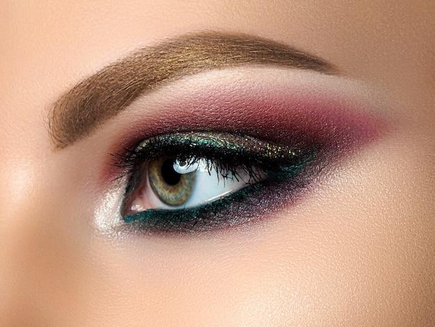 Zbliżenie piękna kobieta oko z wielobarwnym makijażem smokey eyes