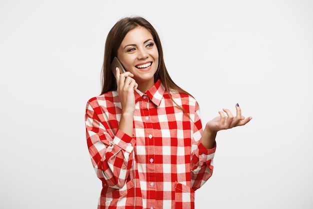 Zbliżenie piękna kobieta opowiada na telefonie w modnej koszula