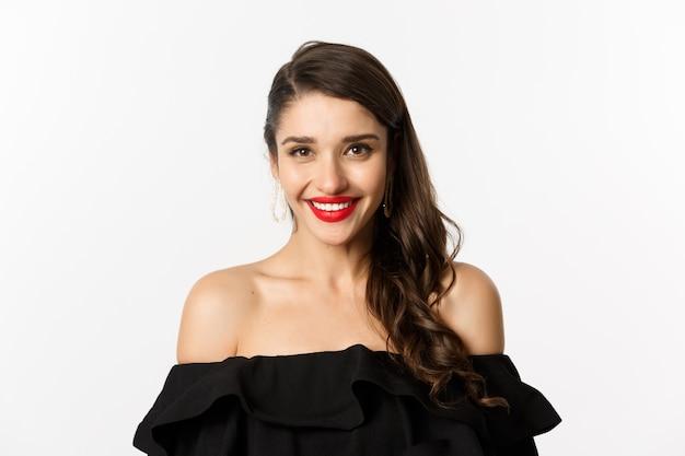 Zbliżenie: piękna kobieta ubrana na imprezę w czarnej sukience, na sobie makijaż i czerwona szminka, uśmiechając się szczęśliwy w aparacie, białe tło.