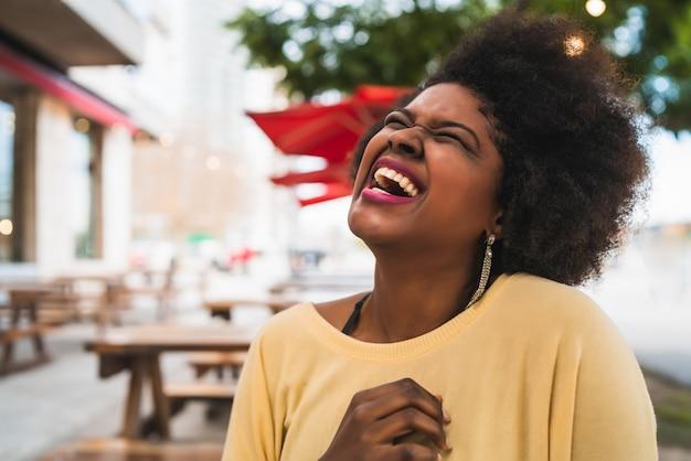Zbliżenie: piękna kobieta z ameryki łacińskiej afro, uśmiechając się i spędzając miło czas w kawiarni.