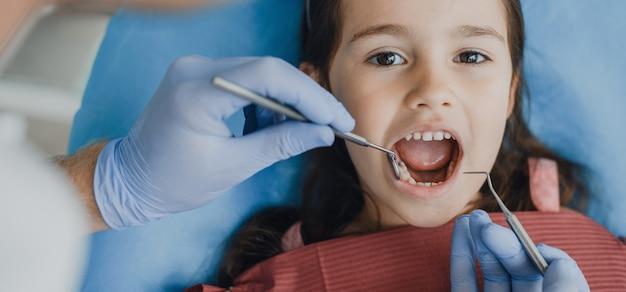 Zbliżenie piękna mała dziewczynka siedzi w fotelu stomatologii po badaniu zębów przez stomatologa dziecięcego.
