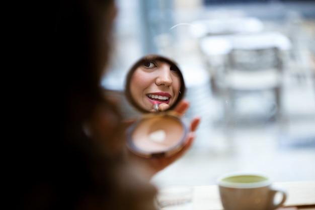 Zbliżenie piękna młoda kobieta odbicie co makijaż w pobliżu lustra w kawiarni.