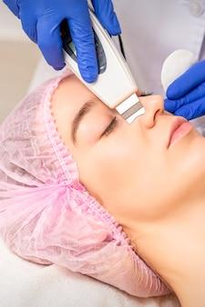 Zbliżenie piękna młoda kobieta odbiera ultradźwiękowe złuszczanie twarzy i peeling kawitacyjny twarzy z urządzeń ultradźwiękowych w biurze kosmetologii.