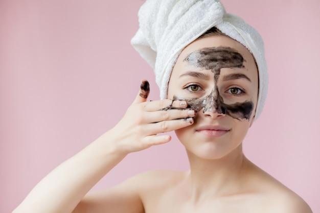 Zbliżenie piękna młoda kobieta z czarną maską peel off na skórze