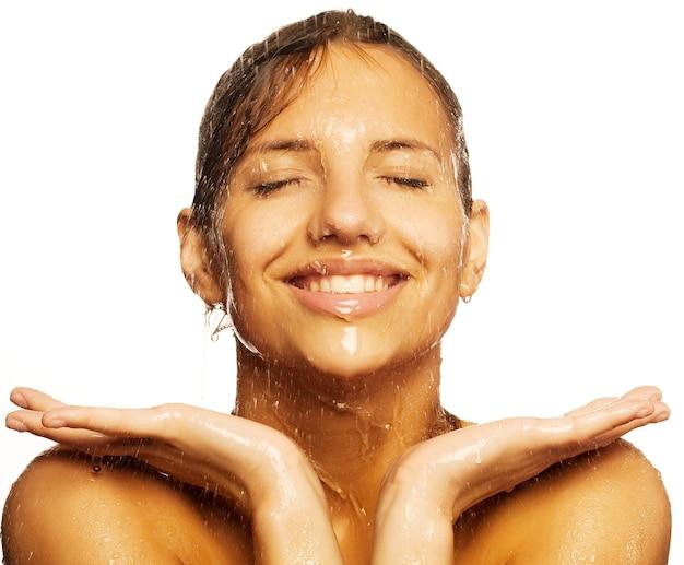 Zbliżenie: piękna mokra twarz kobiety z kropli wody. na białym tle