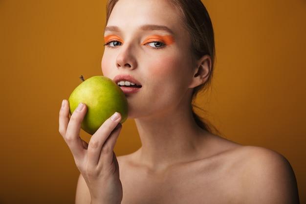 Zbliżenie piękna portret pięknej zmysłowej młodej kobiety odizolowanej na beżowym tle, trzymającej zielone jabłko