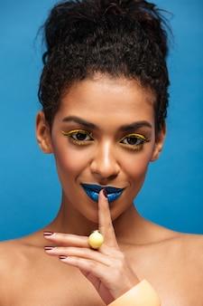 Zbliżenie piękna portret półnagiej afrykańskiej kobiety z makijażem mody, prosząc o milczenie lub tajne kładzenie palca na ustach na białym tle, nad niebieską ścianą