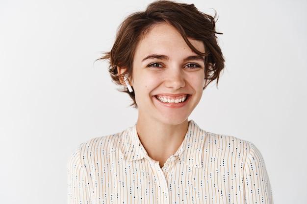 Zbliżenie: piękna szczera kobieta uśmiechająca się i wyglądająca na szczęśliwą, słuchająca muzyki lub podcastu w bezprzewodowych słuchawkach, nosząca słuchawki na białej ścianie