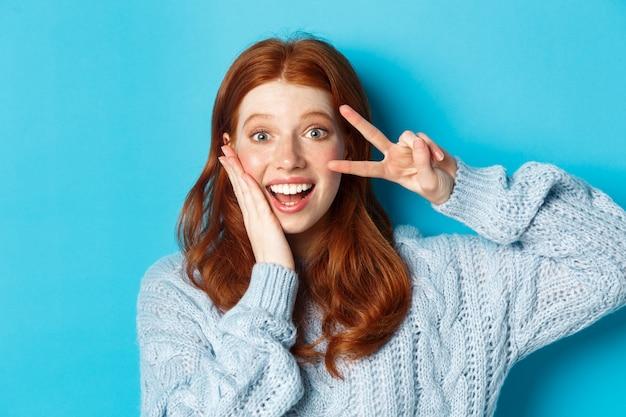 Zbliżenie: piękna uśmiechnięta dziewczyna z rudymi włosami, pokazująca znak pokoju kawaii i wpatrująca się w kamerę, stojąca na niebieskim tle.