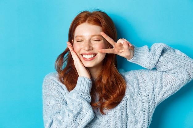 Zbliżenie: piękna uśmiechnięta dziewczyna z rudymi włosami, pokazująca znak pokoju kawaii, stojąca z zamkniętymi oczami na niebieskim tle.