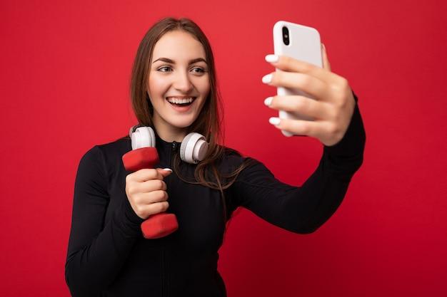 Zbliżenie piękna uśmiechnięta pozytywna młoda kobieta ściany na sobie czarne białe sportowe ubrania
