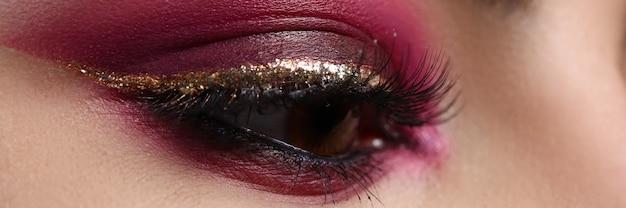 Zbliżenie: piękne kobiece oko z seksowną złotą wyściółką. koncepcja makijaż i kosmetyki. makro błyszczące cienie do powiek na ładnej damy. piękno idealnej twarzy i podkładu