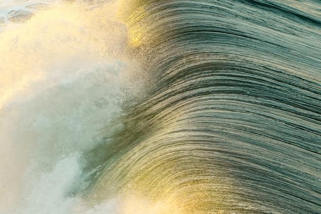 Zbliżenie piękne morze macha bryzgać podczas słonecznego dnia przy plażą