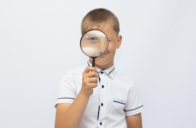 Zbliżenie pięknego dziecka patrzącego przez pętlę szkła powiększającego nad białym