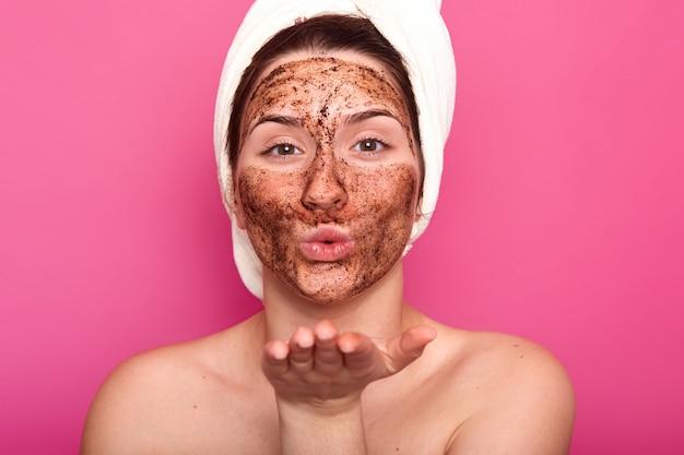 Zbliżenie pięknego europejskiego pocałunku kobiecej dmuchania, zakładania czekoladowej maski na twarz, bycia nagą, czubka włosów z białym ręcznikiem, wygląda na spokojną i zrelaksowaną. pojęcie piękna i pielęgnacji.