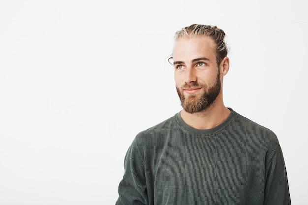 Zbliżenie pięknego męskiego faceta o jasnych włosach, modnych włosach i brodzie w szarej koszuli uśmiechniętego i patrzącego na bok z przyjemnym wyrazem twarzy.