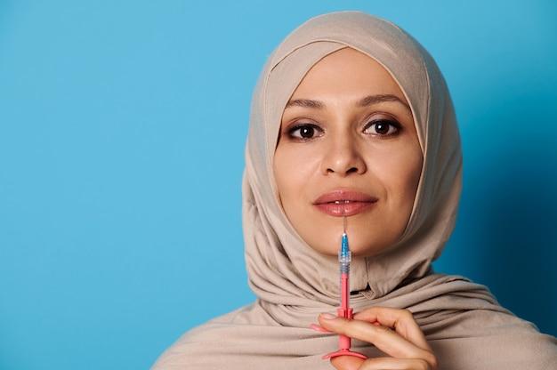 Zbliżenie pięknej arabskiej muzułmańskiej kobiety z zakrytą głową w hidżabie, trzymając strzykawkę z zastrzykiem piękna w pobliżu jej ust