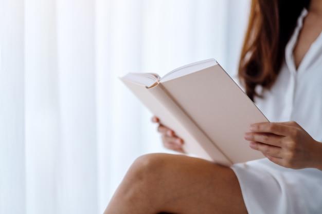 Zbliżenie pięknej azjatykciej kobiety czytelnicza książka w sypialni w domu