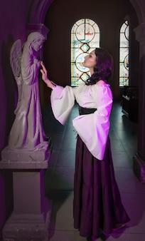 Zbliżenie pięknej cyganki w ciemnym pokoju kościoła katedralnego z tamburynem muzycznym w dłoni