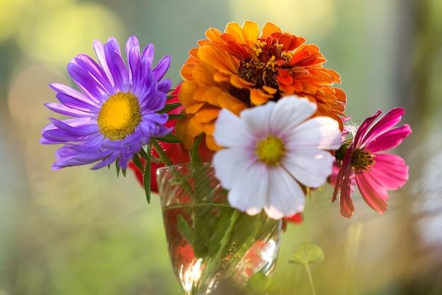Zbliżenie pięknej jesiennej jasnej, wielobarwnej kompozycji kwiatów polnych w przezroczystym szklanym wazonie na zewnątrz na niewyraźne słoneczne