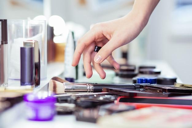 Zbliżenie pięknej kobiecej dłoni dotykającej pędzla do makijażu