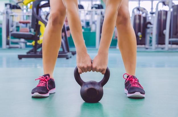 Zbliżenie pięknej kobiety gotowej do podnoszenia czarnego żelaza kettlebell w treningu crossfit na centrum fitness