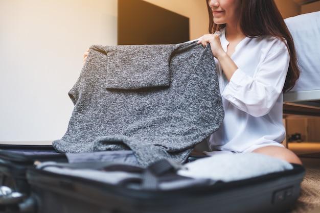 Zbliżenie pięknej kobiety składanie ubrań i pakowanie bagażu na wycieczkę