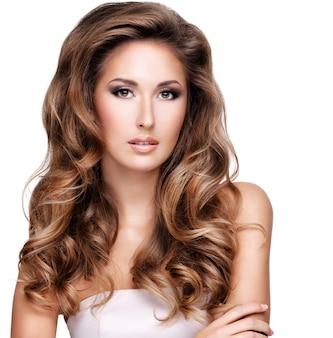 Zbliżenie pięknej kobiety z długimi brązowymi falowanymi włosami, na białym tle