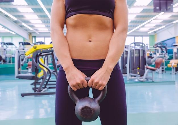 Zbliżenie pięknej kobiety z szczupłą talią i czarną odzieżą sportową trzymającą czarny żelazny kettlebell w centrum fitness