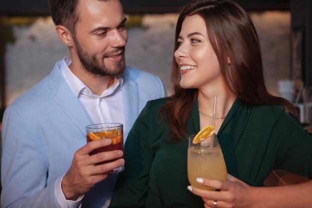Zbliżenie pięknej miłości para uśmiecha się do siebie, ciesząc się napojami w barze koktajlowym