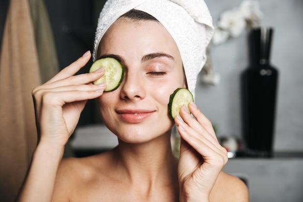 Zbliżenie pięknej młodej dziewczyny z ręcznikiem owiniętym wokół głowy, trzymając pokrojony ogórek na twarzy w łazience