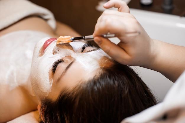Zbliżenie pięknej młodej kobiety opierając się z zamkniętymi oczami, jednocześnie relaksując się, wykonując zabiegi na twarz w centrum odnowy biologicznej.