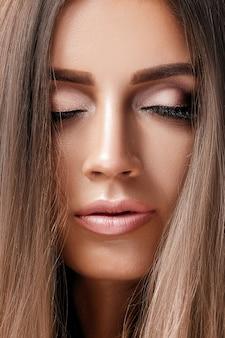 Zbliżenie pięknej opalonej kobiety o perfekcyjnym makijażu i gładkiej skórze. różowy makijaż oczu
