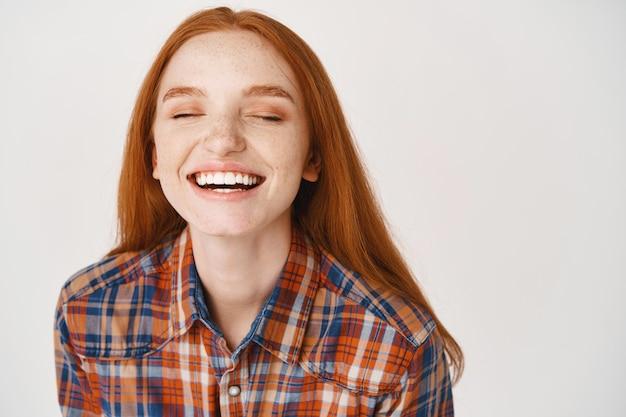 Zbliżenie pięknej rudej kobiety śmiejącej się z zamkniętymi oczami, stojącej nad białą ścianą