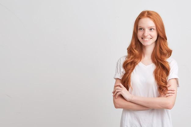Zbliżenie pięknej rudowłosej młodej kobiety z falistymi długimi włosami i piegami nosi koszulkę, jest smutna i patrzy na przód odizolowany na białej ścianie