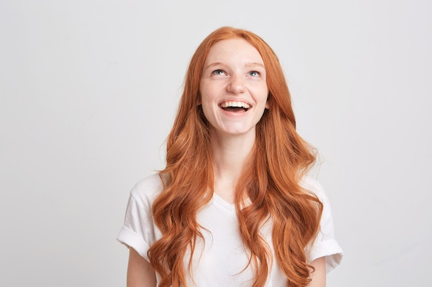 Zbliżenie pięknej rudowłosej młodej kobiety z falistymi długimi włosami i piegami nosi koszulkę, jest smutna i patrzy w górę na białym tle nad białą ścianą
